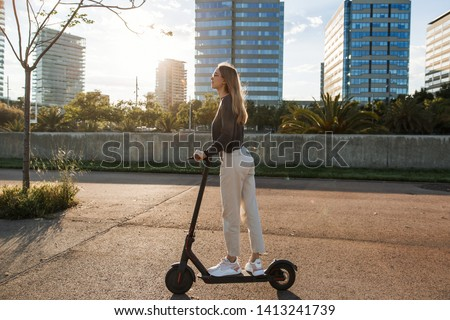 Young beautiful woman riding an electric scooter to work, modern girl, new generation, electric transport, ecology, ecological transport, sunset, electric skateboard, 4k #1413241739