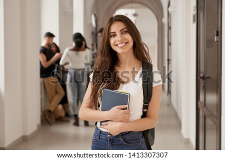 Positivity beautiful girl smiling at camera, standing on corridor with notes as backpack, going to lesson. Happy brunette female student studying in luxury university. Royalty-Free Stock Photo #1413307307