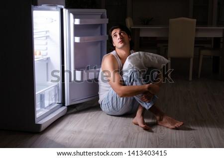 Man breaking diet at night near fridge #1413403415