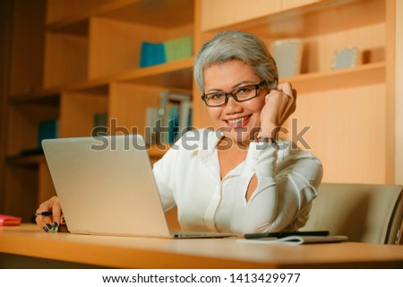 natural lifestyle office portrait of attractive and happy successful mature Asian woman working relaxed  at laptop computer desk smiling confident in business and financial success  #1413429977