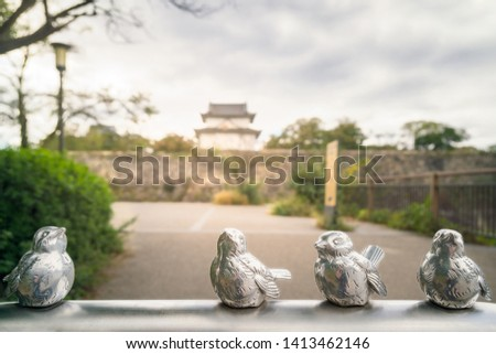 Silver bird sculptures at Osaka Castle Park in the foreground with the moat and fortifications of Osaka Castle blurred in the background. Osaka Castle is one of the most famous landmarks in Japan.
