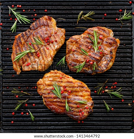 Grilled pork steaks, pork neck with the addition of herbs and spices on the grill plate, top view, Grilled meat, bbq, barbecue #1413464792