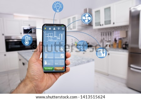 Close-up Of Man's Hand Holding Mobile With Smart Home Control Icon Feature With Kitchen Background #1413515624