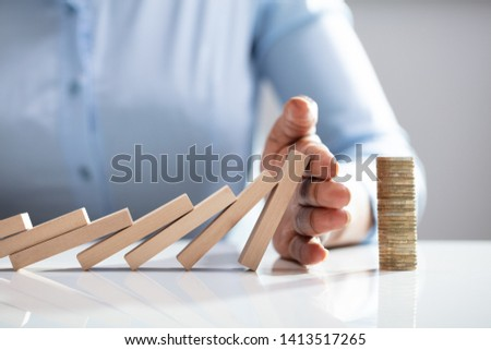 Human Finger Stopping Dominos From Falling With Stacked Coins On White Desk #1413517265