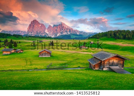 Alpe di Siusi - Seiser Alm with Sassolungo - Langkofel mountain group at sunset. Picturesque summer alpine landscape and wooden chalets in Dolomites, Trentino Alto Adige, South Tyrol, Italy, Europe #1413525812