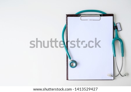 Blank medical clipboard with stethoscope on white background. Copy space. Royalty-Free Stock Photo #1413529427
