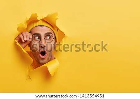 Astonished unshaven man gazes through hole in yellow paper, wears round spectacles, opens mouth with surprisement, copy space to insert text or slogan. Effect of torn paper. Discount and sale #1413554951