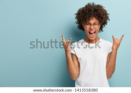 Emotive dark skinned woman makes rock n roll sign, says I will rock this party, yells loudly, wears round spectacles, casual t shirt, stands over blue background with empty space, feels self confident #1413558380