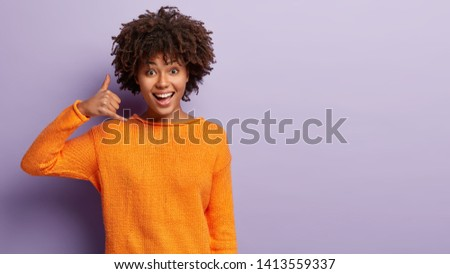 Delighted young female model with happy expression, makes call gesture, asks being in touch, wears casual orange jumper, isolated over purple background with free space for your advertisement #1413559337