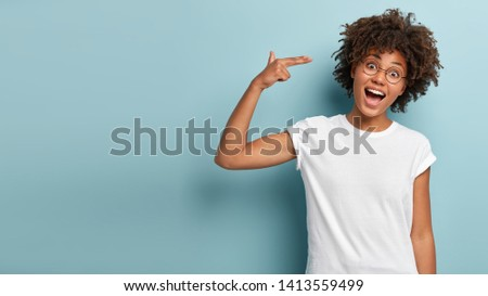 Glad dark skinned curly woman shoots in temple, tilts head, keeps mouth widely opened, dressed in casual white t shirt, demonstrates suicide gesture, isolated on blue background with blank space #1413559499