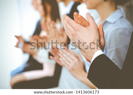 Business people clapping and applause at meeting or conference, close-up of hands. Group of unknown businessmen and women in modern white office. Success teamwork or corporate coaching concept #1413606173