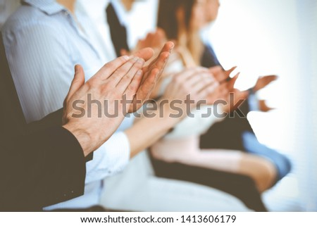 Business people clapping and applause at meeting or conference, close-up of hands. Group of unknown businessmen and women in modern white office. Success teamwork or corporate coaching concept #1413606179