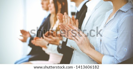 Business people clapping and applause at meeting or conference, close-up of hands. Group of unknown businessmen and women in modern white office. Success teamwork or corporate coaching concept #1413606182