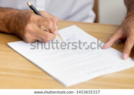 Close up caucasian male hands holding pen singing business paper, contract sitting at desk. Confirmation and accepting collaboration or hiring employment agreements, lease mortgage, insurance concept #1413631157