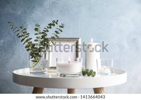 Composition with burning aromatic candles on table near color wall Royalty-Free Stock Photo #1413664043