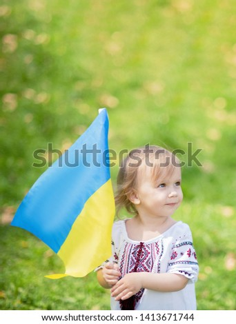 Child carries fluttering blue and yellow flag of Ukraine in field. Ukraine's Independence Day. Flag Day. Constitution day. Girl in traditional embroidery with flag of Ukraine #1413671744