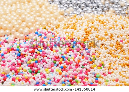 Small colored sugar sprinkles of various types isolated on white background. Used as a decoration or to add texture to cupcakes, cookies, cakes, doughnuts, ice cream, frozen yogurt and puddings. Royalty-Free Stock Photo #141368014