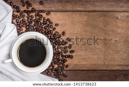 A cup of hot coffee on a folded white cloth and an old wooden table #1413738623
