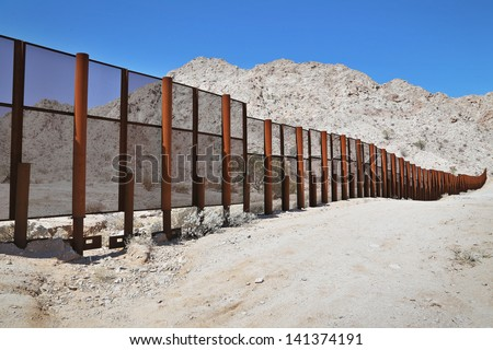 Large steel fence protecting the border between Mexico and the United States of America at the Tinajas Altas Mountains in Arizona (Sonoran Desert). Common place for illegals & drug smugglers to cross. #141374191