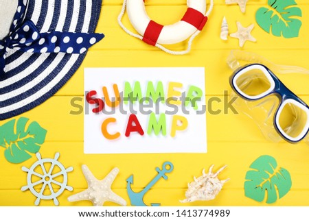 Text Summer camp with seashells, hat and diving mask on yellow wooden table #1413774989