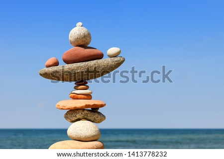 Rock zen pyramid of colorful pebbles on a beach on the background of the sea. Concept of Life balance, harmony and meditation #1413778232