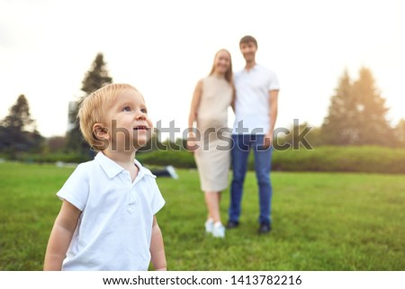A boy with a toy on the background of parents in the park. #1413782216