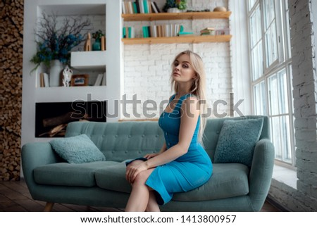Young woman in sexy dress is sitting on a couch. Sensual beautiful blonde woman posing in blue dress. Girl with long hair. Indoor shot. #1413800957