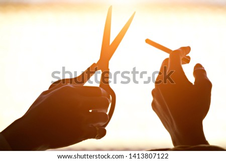The hand holding the cigarette and the hand holding the scissors, with the orange light of the sun behind, saw a black shadow. #1413807122