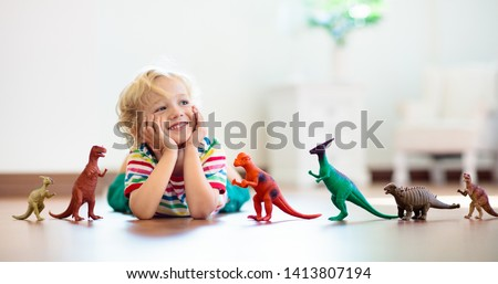 Child playing with colorful toy dinosaurs. Educational toys for kids. Little boy learning fossils and reptiles. Children play with dinosaur toys. Evolution and paleontology game for young kid. #1413807194