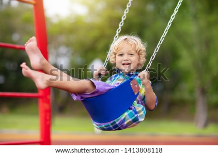 Child playing on outdoor playground in rain. Kids play on school or kindergarten yard. Active kid on colorful swing. Healthy summer activity for children in rainy weather. Little boy swinging. #1413808118