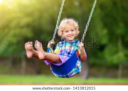 Child playing on outdoor playground in rain. Kids play on school or kindergarten yard. Active kid on colorful swing. Healthy summer activity for children in rainy weather. Little boy swinging. #1413812015
