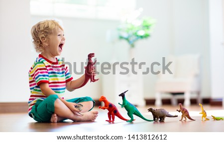Child playing with colorful toy dinosaurs. Educational toys for kids. Little boy learning fossils and reptiles. Children play with dinosaur toys. Evolution and paleontology game for young kid. #1413812612