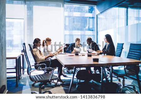 Multiethnic men and women with papers working in team while creating new project sitting at table in office boardroom and talking #1413836798
