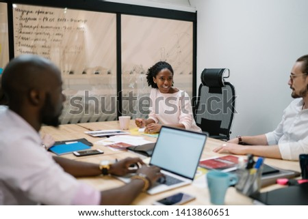 Successful multicultural male and female finance professionals coworking together near office desktop discussing details for management startup project, concept of entrepreneurship and teamwork #1413860651