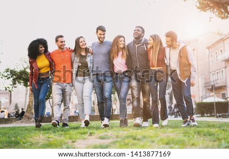 Mixed race group of friends having fun walking outdoors hand on shoulders. Young people community walking together. Integration and diversity concept. #1413877169