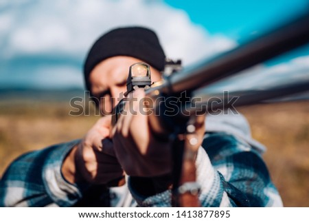 Hunter Target with laser sight. Collimating sight. Hunter with shotgun gun on hunt. Hunter Target with laser sight. Hunter aiming rifle in forest. Poacher in the Forest #1413877895