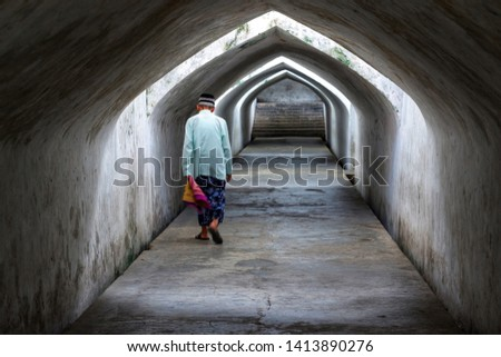 Elderly/old man wearing Muslim clothing, sarongs and cap is walking in the Taman Sari Water Castle hallway after praying with Ray of light from the vents. Back view. #1413890276