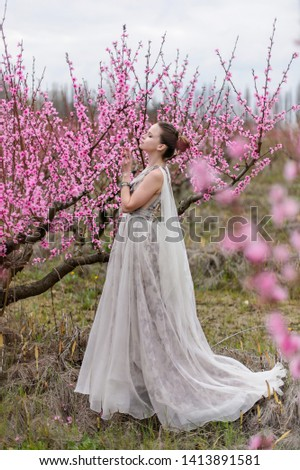 Beautiful girl in amazing dress in the gardens. #1413891581