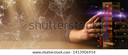 business man try to build wood block on wooden table and black background business organization strategy startup concept Royalty-Free Stock Photo #1413906914