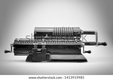 Ancient pinwheel mechanical calculator.This is a mechanical device used to perform automatically the basic operations of arithmetic, rendered obsolete by electronics calculators.Black and white shot. #1413919985
