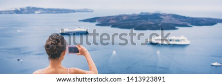 Travel tourist taking holiday picture with phone of cruise ships in Mediterranean sea in Santorini, Greece. Europe vacation destination banner panorama.