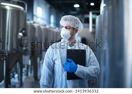 Technologist in protective white suit with hairnet and mask standing in food factory. Royalty-Free Stock Photo #1413936332