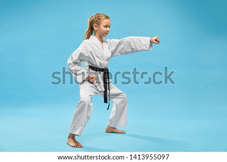 Karate girl standing in stance and punching with hand in studio. Positive, confident child in kimono with black belt practicing karate and jujitsu on blue isolated background. Royalty-Free Stock Photo #1413955097