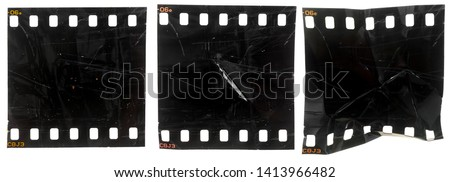 set of three black and exposed 35mm filmstrips or snips with scratches and marks on white background, rumpled film material #1413966482