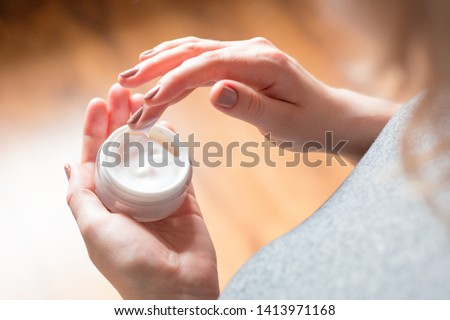 young woman uses body care cream #1413971168