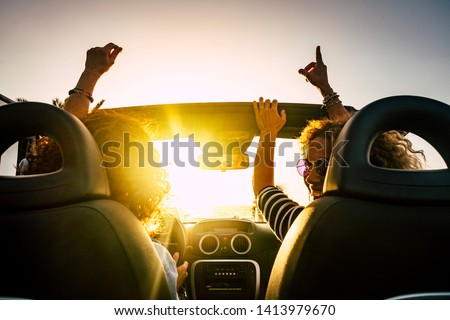 People joy and happy driving and traveling for summer holiday vacation and outdoor leisure activity with convertivle car laughing and dancing like crazy - sunlight in the glass and travel concept #1413979670