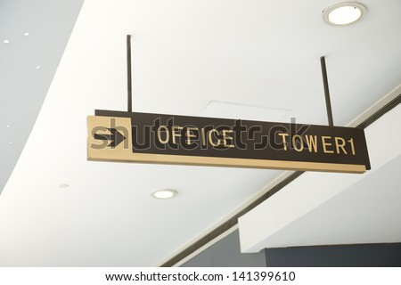 Office sign suspended from the ceiling of corridor.