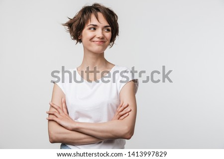 Image of optimistic woman in basic t-shirt smiling and looking aside while standing with arms crossed isolated over white background #1413997829