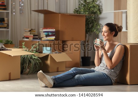 Happy tenant resting drinking coffee moving home sitting on the floor in the night Royalty-Free Stock Photo #1414028594