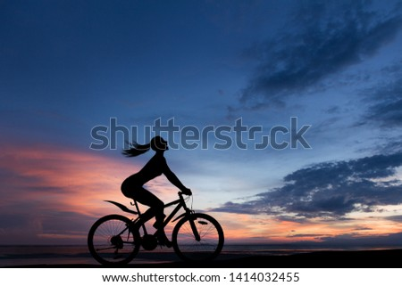 Silhouette photo of young woman riding on bicycle with sunset cloudy sky in background #1414032455